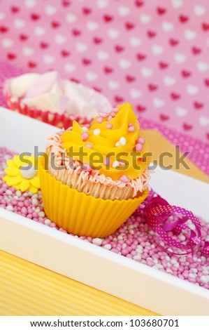Yellow cupcake in a romantic pink love Valentine setting - stock photo