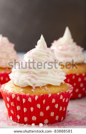 Yellow cupcake in red and white polka dot cupcake paper topped with white frosting