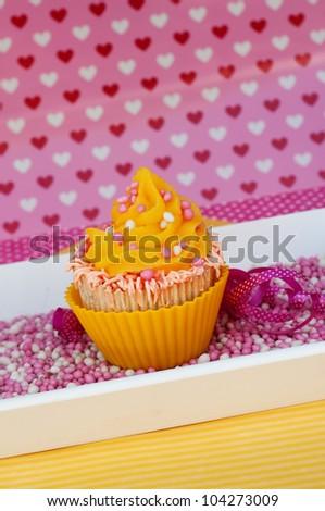 yellow cupcake on pink rusk - stock photo
