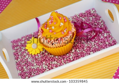 Yellow cupcake with pink baby girl rusk on a plateau - stock photo