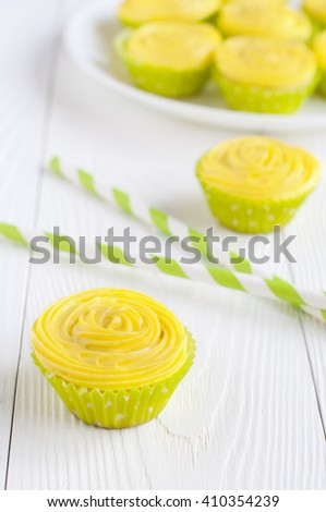 Yellow cupcakes in light green paper liners on wooden table. Selective focus - stock photo