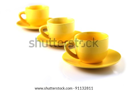 Yellow cups on row, on white background