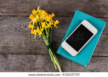 Yellow daffodils, notebook and mobile phone on the table. - stock photo
