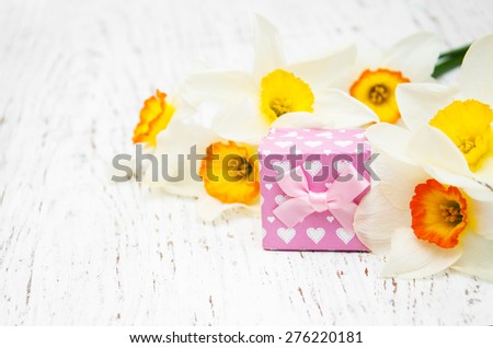 Yellow daffodils with present box on a old wooden background - stock photo