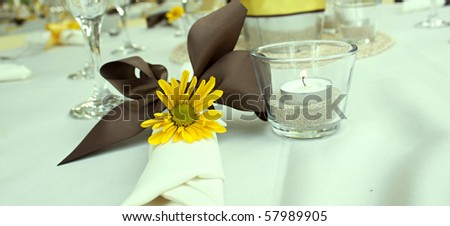 Yellow Daisy table setting with a brown bow - stock photo