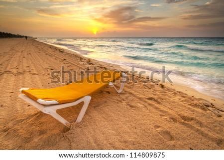 Yellow deckchair on the Caribbean Sea at sunrise - stock photo