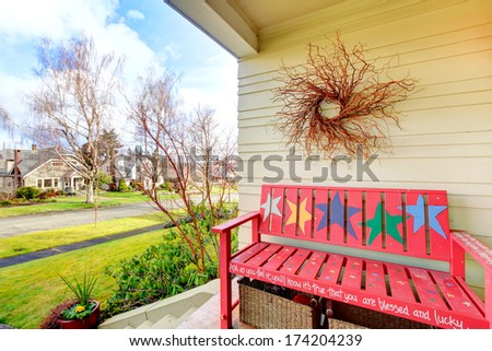 Yellow decorated porch with red bench, wicker baskets, dry branch, overlooking the front view - stock photo