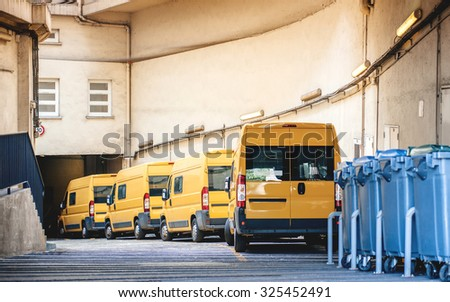 Yellow delivery vans in a row service van, trucks and cars in front of the entrance of a warehouse distribution logistic plant - stock photo