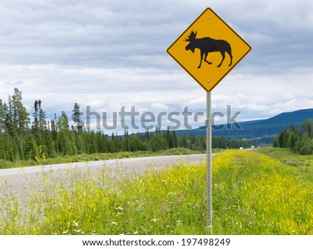 Yellow diamond traffic road sign warning, Attention moose crossing, posted alongside a scenic rural country road in lush countryside