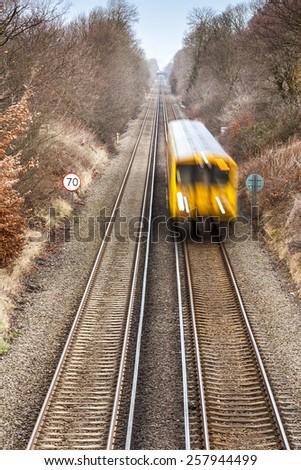 Yellow diesel passenger train speeds towards - stock photo