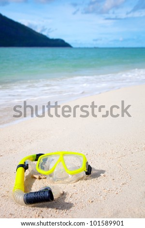 Yellow diving mask on the beach by the blue sea - stock photo