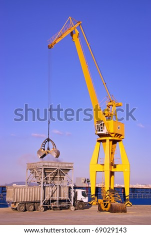Yellow dock crane unloading material from a cargo ship - stock photo