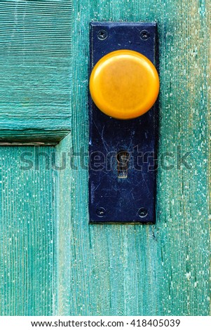Yellow Door Knob on Green Blue Door - stock photo