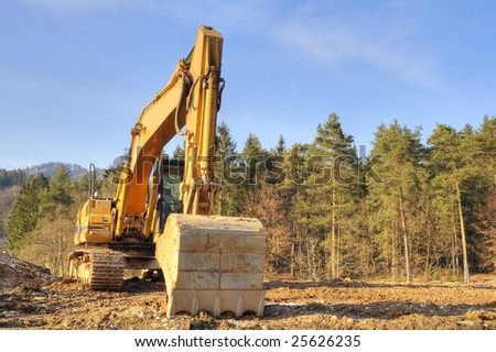 Yellow dredger on construction ground against forest and sky. - stock photo