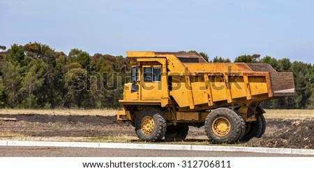 Yellow dump truck - stock photo