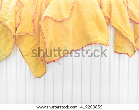 Yellow dusting cloths drying on a radiator