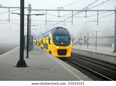 Yellow Dutch train and central station platform in Amsterdam - stock photo