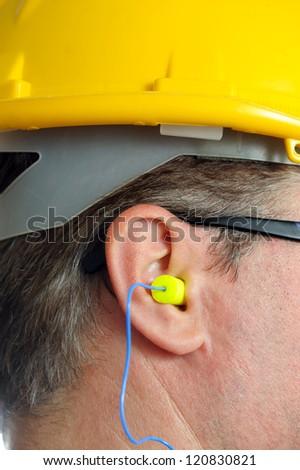 yellow earplug into the ear - stock photo