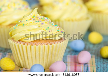 Yellow Easter cupcake with sprinkles and candy eggs. Closeup with shallow depth of field.