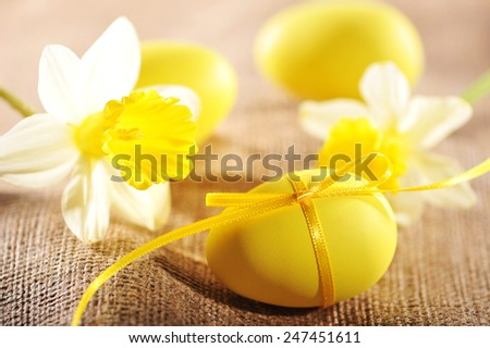 Yellow Easter eggs with bow on jute bag with narcissus - stock photo