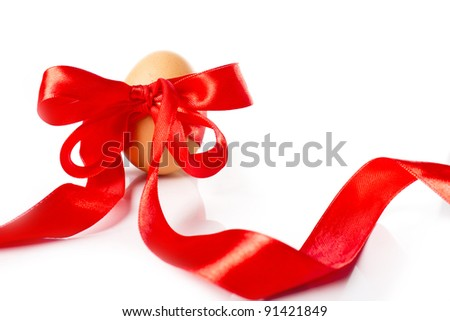 Yellow egg bounded in red ribbon. Isolated on white