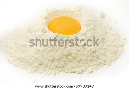 yellow egg yolk in the flour isolated on white background - stock photo