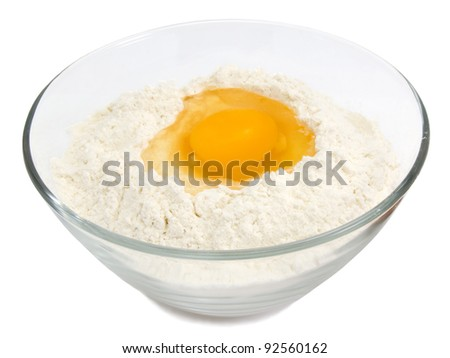 Yellow egg yolk in the flour isolated on white background