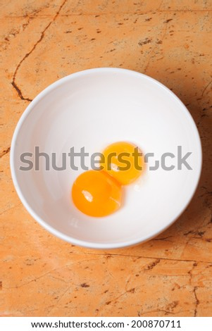 yellow egg yolks in a white bowl on table - stock photo