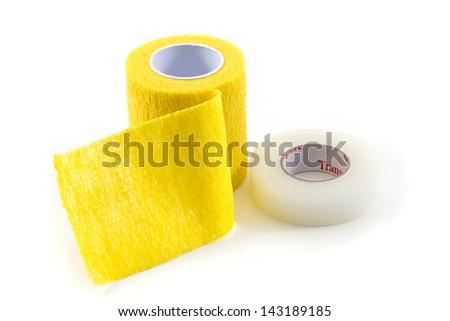 Yellow Elastic Medical Bandage and adhesive tape on White Background - stock photo