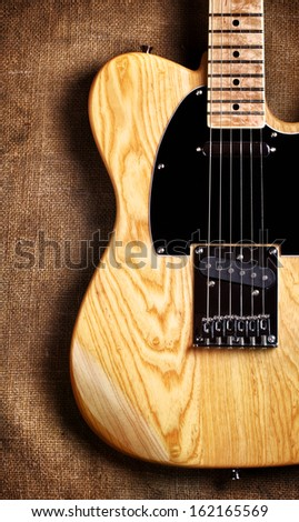 yellow electric guitar on brown canvas background - stock photo