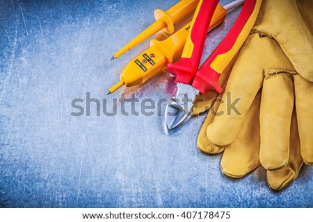 Yellow electrical tester safety gloves red wire cutter on metallic background electricity concept. - stock photo