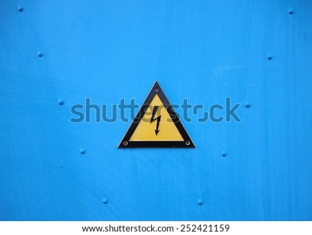 Yellow Electrical Warning Triangle Sign on Blue Background with Rivetter - stock photo
