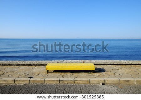 Yellow empty bench on blue sea background - stock photo