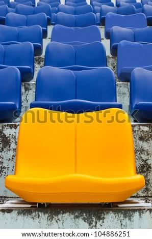 Yellow empty plastic seats at stadium - stock photo