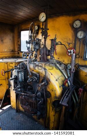 Yellow engine room on the steam locomotive - stock photo