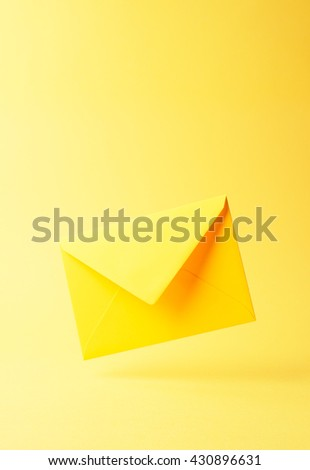 Yellow envelope dropped over yellow background