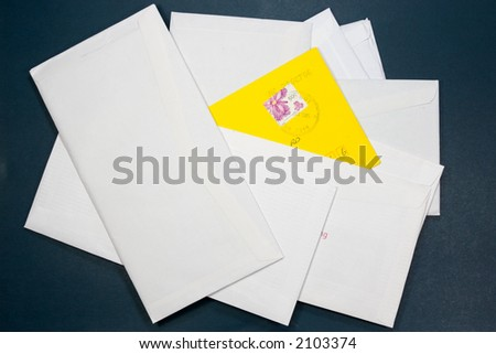 Yellow envelope in the heap of mail - stock photo