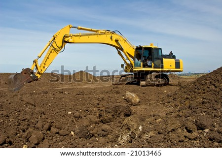 Yellow Excavator against a blue sky.