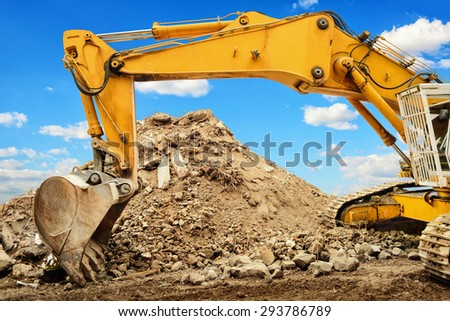 Yellow excavator and a heap of dirt, in the background a nice blue sky with white clouds - stock photo