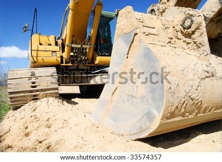 yellow excavator, digger on blue sky - stock photo