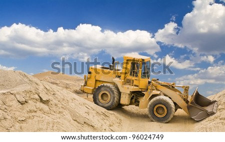yellow excavator in quarry - stock photo