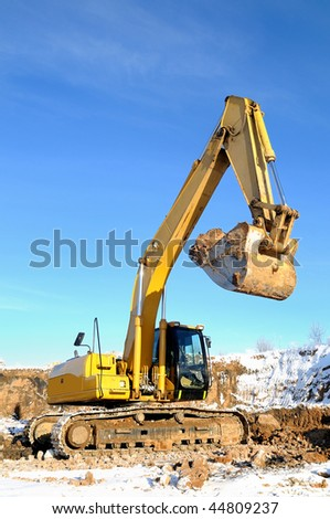 Yellow excavator loader at construction site with raised bucket in winter