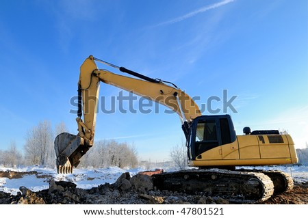 Yellow excavator loader at construction site with raised bucket over blue sky - stock photo