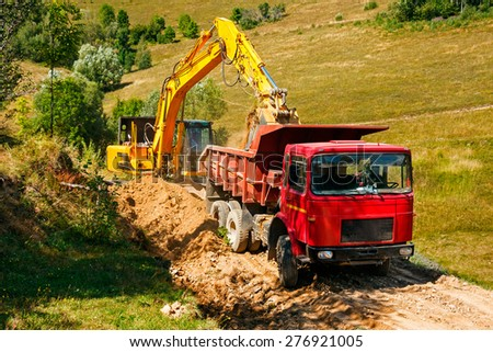 yellow excavator loading soil on a truck while building a mountain road - stock photo
