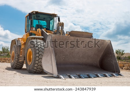Yellow excavator on a construction site against blue sky - stock photo
