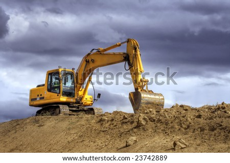 Yellow excavator on a hill - stock photo