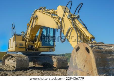 yellow excavator on blue sky background - stock photo