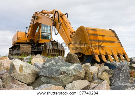 yellow excavator on top of big heap of stones, close up - stock photo