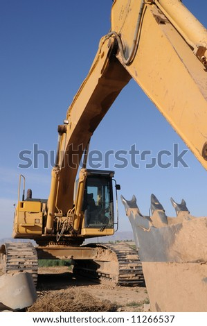yellow Excavator shown from from front digger vertically