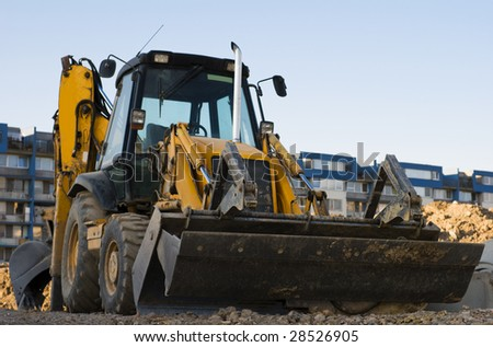 Yellow excavator with a backhoe